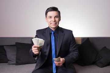 Młody mężczyzna liczy pieniądze - finanse nieruchomości inwestycje