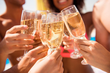 Diversity international entertainment season festive  event cheerful joyful smiling victory win tourism travel concept. Close up  cropped photo of people's hands clinking glasses full of champagne