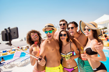 Alcohol glasses holiday leisure toothy mad people blue sky sea concept. Six excited cheerful attractive active joking friendly people taking self portrait against swimming pool with chaise-longues