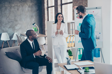 Handsome man in glasses with stubble making advances to his beautiful colleague, lean with hand on flipchart, white board, three partners speaking during free time holding mug with tea in hands