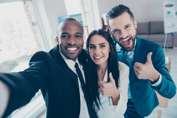 Three funny, cheerful friends having free time,  showing like symbol, afroamerican black man with bristle shooting selfie on front camera of smart phone, together standing in workplace, workstation
