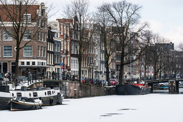 Stunning view of Amsterdam canals and house boat frozen with snow during the cold wave in February 2018 on a very cold winter day.