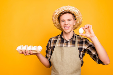Close up portrait of kind emotion expressing cheerful excited joyful rejoicing farmer holding half-carton with eggs and demonstrating one fresh tasty delicious egg in hand isolated bright background