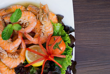 Bake shrimp with salt in white dish which has fresh vegetables decorated on dish
