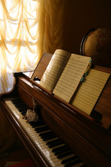 Opened grand piano with a doll on the keyboard and notes on a stand in the soft warm light in a room next to the window, decorated by stylish curtain. Sphere globe in a dark corner.