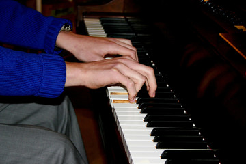 Male hands playing piano closeup. Hands of a young caucasian male piano player in casual outfit playing piano.