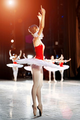 Unknown ballerina in white tutu  on the stage  behind the scenes before the show begins.  warm up before the performance