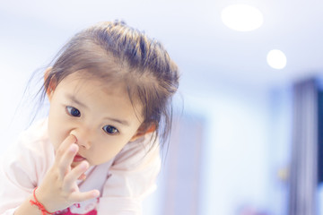 Little girl picking a nose between watching something in tablet in her house.