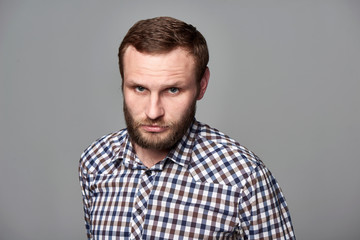 Portrait of severe bearded man in checkered shirt standing on gray background staring at camera