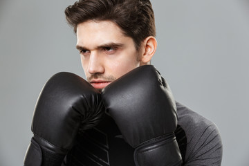 Concentrated young sportsman boxer make sport exercises wearing gloves.