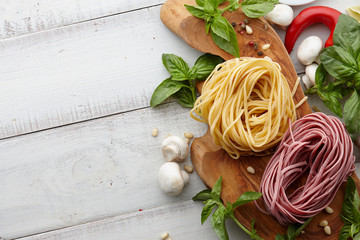 Raw homemade italian pasta and ingredients on white wooden background, cooking process