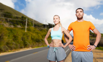fitness, sport and healthy lifestyle concept - happy couple exercising over big sur hills and road background in california