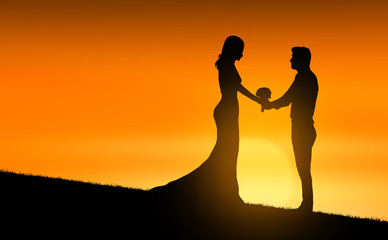 married couple in silhouette at sunset