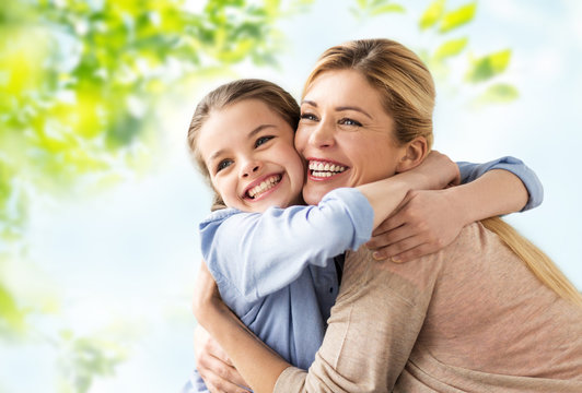 people and family concept - happy smiling mother hugging daughter over green natural background