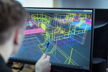 Worker looking at CAD wireframe industrial design on screen