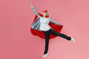 Young attractive woman superhero. Girl in a business suit and a mask with red cloak of hero.