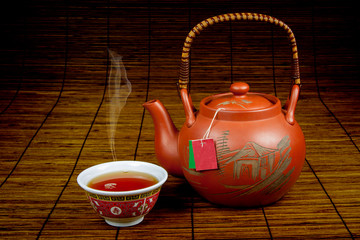 Pouring Chinese tea with an authentic Chinese teapot and cup on a bamboo background
