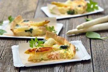 Streetfood: Leckerer Tarte mit frischem weißem Spargel, Räucherlachs und Spinat auf Pappteller - Baked quiche with fresh whitehasparagus, smoked salmon and spinach