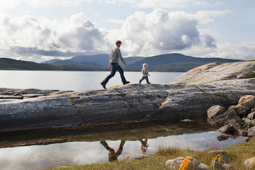 Man and son walking on fjord rock formation, Aure, More og Romsdal, Norway