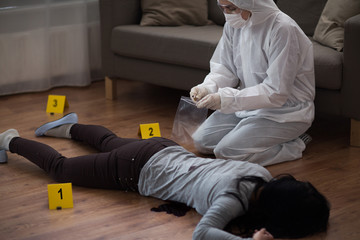 investigation, forensic examination and people concept - criminalist collecting evidence of murder at crime scene (staged photo)