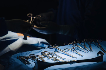 close up of surgical instrument lying on table while group of surgeon work in operation room at hospital, emergency case, surgery, medical technology, health care cancer and disease treatment concept