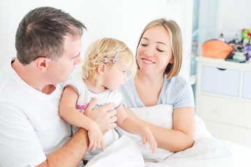 Happy and loving family morning concept. Cheerful parents in sleepwear having fun with their daughter on the bed. Family spending free time together at home.Soft selective focus. Space for text.