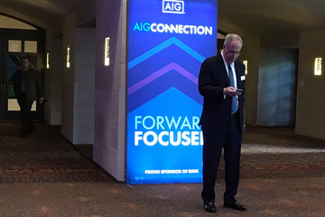 A man checks his phone at the AIG Inc and the Risk Management Society annual conference in San Antonio