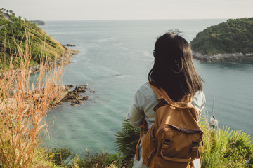 Young traveler woman standing and looking at view enjoying a beautiful of nature at top of mountain and sea view,Freedom wanderlust backpacker concept,vintage filter