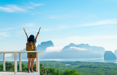 Happy young traveler woman backpacker raised arm up to sky enjoying a beautiful of nature at mountain panorama view point and sea,Freedom wanderlust,Khao Samed Nang Chee Viewpoint,Phang Nga,Thailand.