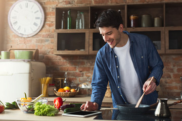 Happy man preparing healthy food in the home kitchen