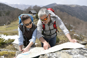 Couple of hikers reading orientation map Wall mural