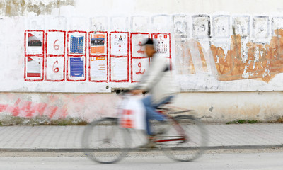 A man rides his bicycle past a wall covered in municipal elections campaign posters in Tunis