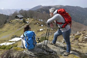 Hikers admiring mountain scenery during trekking day