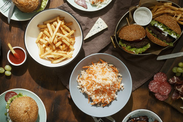 Dinner outdoor table with burger, french fries, salad and snacks on wooden table, top view