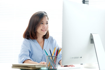 Young asian businesswoman working with laptop computer at office with happy emotion, working at home, office casual lifestyle concept