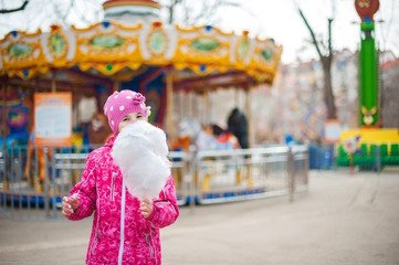 A photograph of a child's rest on nature in the spring. A child girl in a bright pink jacket is eating sweet cotton wool against the backdrop of rides, carousels. Close-up portrait with sweet cotton w