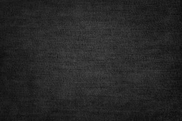 Black jeans texture. Dark fabric background.