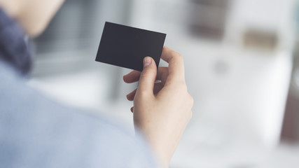Woman holding the business card