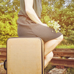 Woman sitting on a suitcase near railway tracks.