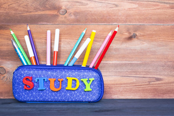 School supplies in a pencil case on the wooden background.