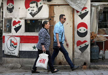 A man and a woman are walk in the old city of Damascus