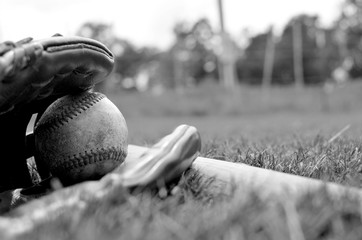 Baseball sport equipment shows ball and leather glove.