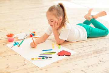 Top view of little blonde girl painting on big white paper while laying on the floor indoors.