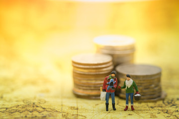 Money, Family Travel Concept. Parent (Male and female) and child miniature figures standing on world map with stack of coins.