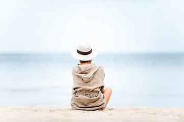 Young beautiful woman in hat contemplating Sea