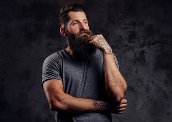 Portrait of a hipster with full beard and stylish haircut, dressed in a gray t-shirt, stands with a thinking look in a studio on a dark background.