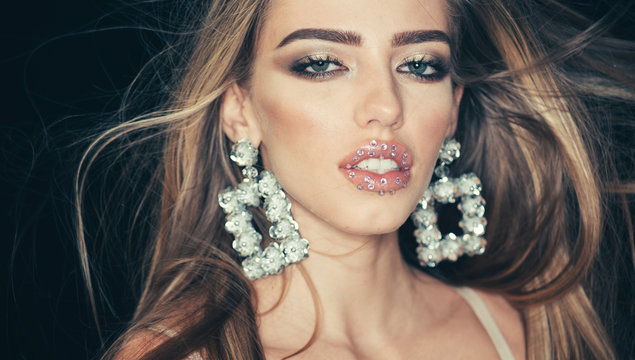 Sparkle Makeup. Close up of beauty fashion girl with silver rhinestones lipstick and glitter eyeshadow, wears in sparkling big earrings jewelry over dark studio background.
