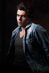 Thinking serious charismatic man in blue jeans looking on dark shadow dramatic light background. Closeup portrait. Art