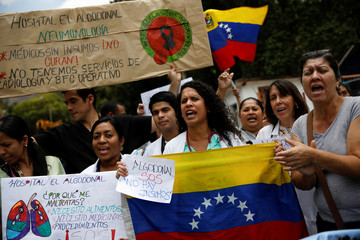 Workers of the health sector take part in a protest due to the shortages of basic medical supplies and for higher wages outside a hospital in Caracas