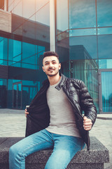 Arabian man taking his coat off in front of modern building. Young man shows off